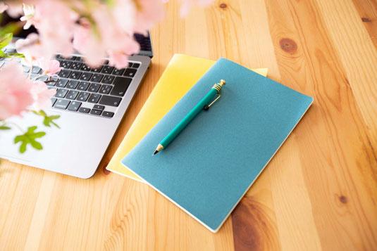ガラスの花びんに活けられた大輪のピンクのバラ。ピンクと白の2冊の手帳。ボールペン。