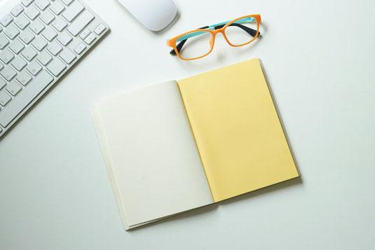 木製のデスク。パソコンのキーボードの前に置かれたボールペン。ガーベラ、コデマリの花。