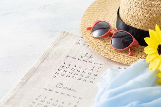 パソコンのキーボード。コーヒーの入ったカップ&ソーサ。リングノート。スマートフォン。手帳とメモ帳。ダブルクリップ。ボールペン。腕時計。観葉植物の鉢植え。