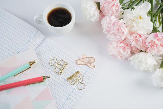 木目調のテーブルに広げられたノートパソコン、付箋、クリップ、ペンケース、ボールペン。仕事中。