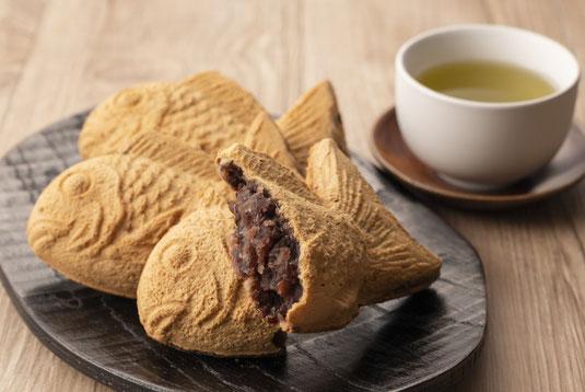 コーヒーの入った白のマグカップ、コーヒー豆、コーヒーミル。コーヒータイム。