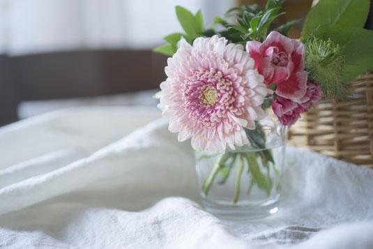 ラグのうえに置かれたパソコンのキーボード、コーヒーの入ったマグカップ。ページが開かれた白紙のノートとボールペン。クッション。観葉植物のグリーン。