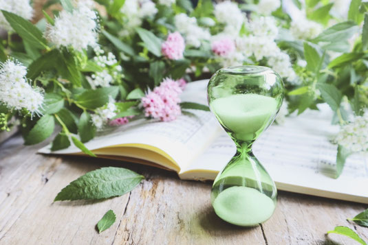 砂時計とページの開かれた楽譜。沈丁花の花。