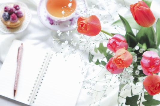 白紙のメモ帳とボールペン。カスミソウとオレンジピンクのチューリップの花びん。紅茶の入ったカップ&ソーサ。ベリーののったカップケーキ。