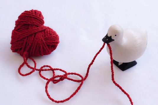 ハート形にまとめられた赤の毛糸。まとめられた毛糸のはじっこをくわえるミニチュアの鳥。