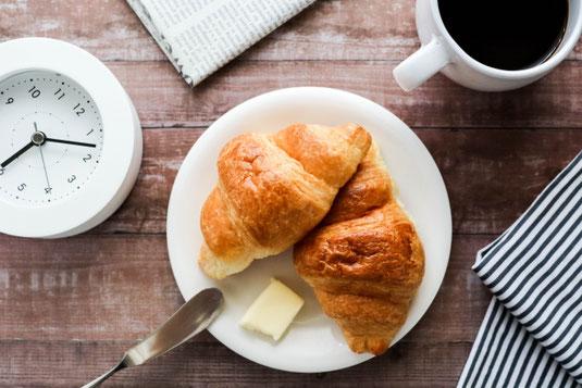 朝食タイム。木製のテーブルに並べられたクロワッサンのお皿、コーヒーの入ったマグカップ、ストライプのナプキン、新聞、置時計。