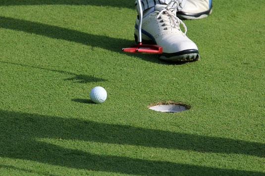 グリーンに載ったゴルフボール。パターとゴルフシューズ。