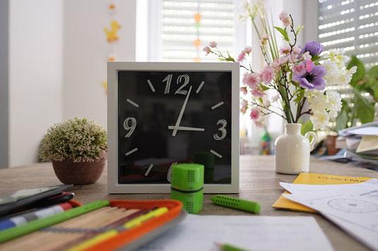 にぎやかなデスクの上。クロック時計、花びん、観葉植物、筆入れ、ペン、メモ書きなどが所狭しと並んでいる。