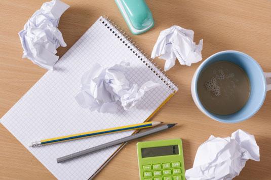 水色のマグカップがひっくりかえって仕事の書類がコーヒーまみれ。めがねと電卓。