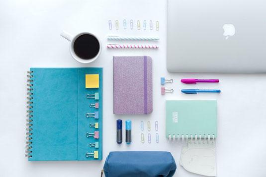 事務デスク。スタンドライト、ペン立て、マグカップ、ノート、パソコンがデスクに並んでいる。