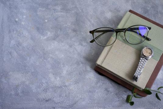 ノートパソコンの前に広げられたシステム手帳と万年筆。マグカップと黒ぶちフレームの眼鏡。