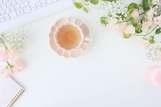 パソコンのキーボードの前に置かれたピンクの花型のカップ&ソーサ。無造作に置かれた薄いピンクのバラのつぼみとカスミソウ。メモ帳。
