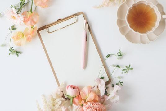 バインダーファイルに綴じられた白紙のレポートパッドとピンクのボールペン。意見聴取。紅茶のはいったピンクのカップ&ソーサ。ピンクのガーベラ、カーネーション、バラの花。