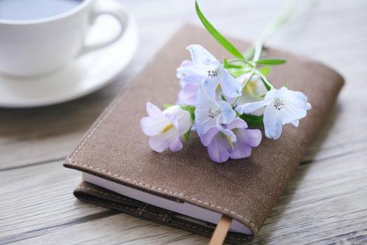 テーブルのうえに置かれた手帳。手帳のうえに置かれた花一輪。カップ&ソーサ。