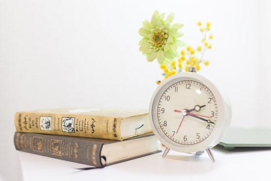 デスクのうえに置かれた手帳。パソコンのキーボード、黒の目覚まし時計、小さな鉢植えの観葉植物。