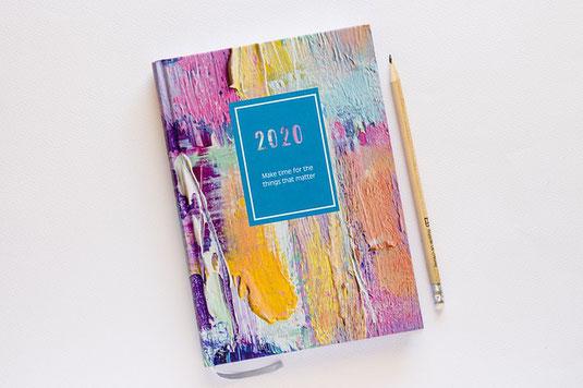 2020年のダイアリー。虹色の絵具調プリントの表紙。えんぴつ。