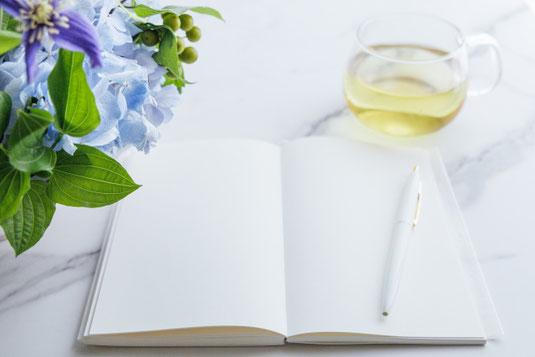 カレンダー、広げられたスケジュール帳、スマホ、ボールペン、置時計。コーヒーの入ったピンクのカップ&ソーサ。ラナンキュラスの花。