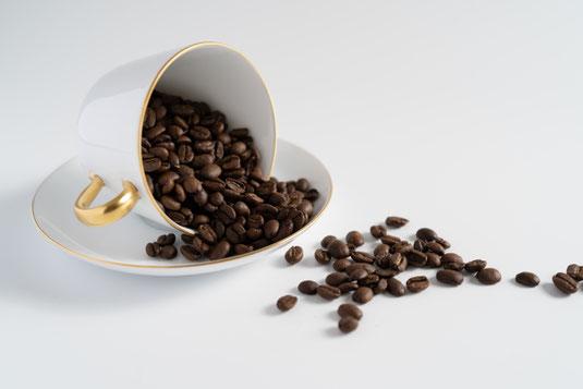 ページが開けられた書籍のうえにコーヒーカップをおいてしまい、コーヒーが波打ちこぼれる様子。周りの置かれた書籍にもコーヒーの飛沫がとびちる。