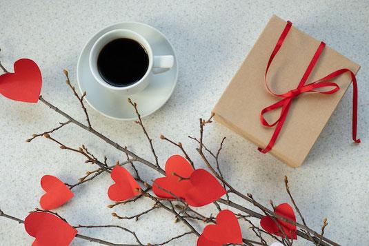 電卓と万年筆。四つ葉のクローバーが飾られたミニチュアハウスのオーナメント。