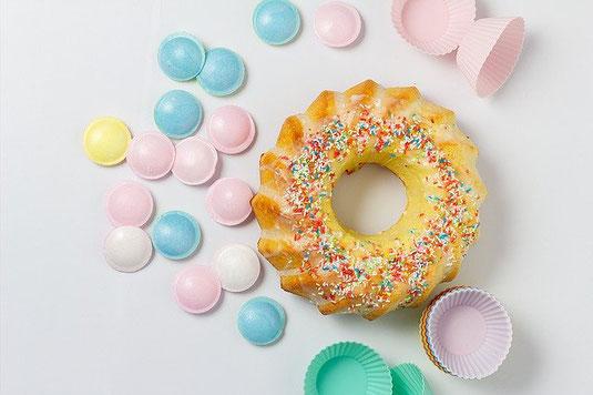ドーナッツとカラフルなラムネ菓子。カップケーキのカップ。