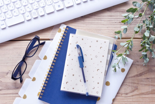 パソコンのキーボード。リーディンググラス。水玉のクリアファイルと青のリング式ノート、メモ帳と青のボールペン。観葉植物のグリーン。