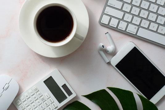 ノートパソコンのまえに広げられたメモ帳とボールペン。眼鏡、マグカップ、観葉植物のグリーン。