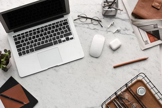ノートパソコンのうえに置かれたスマートフォン。広げられたリングノートと定規、サインペン。コーヒーの入ったマグカップ。白のチューリップが一輪。