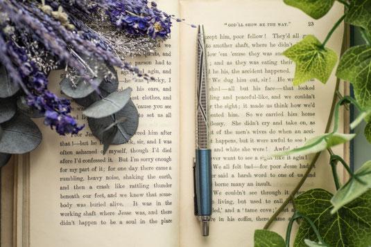 ページが開かれた洋書のうえに置かれたボールペン。紫のドライフラワーと観葉植物のつる。