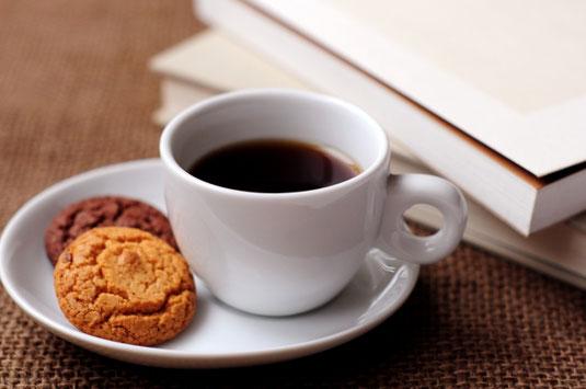 ノートパソコンとブラックコーヒーのマグ。リングノートの上に置かれたべっ甲フレームの眼鏡。