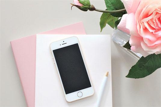 ガラスの花びんに活けられた大輪のピンクのバラ。積まれた手帳のうえに置かれたスマホとボールペン。