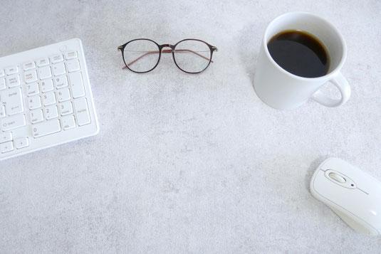 ノートパソコン。コーヒーの入った赤のマグカップ。縦書きの便箋と万年筆。観葉植物のグリーン。