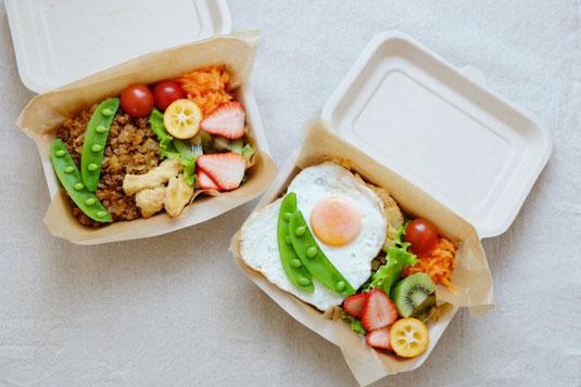 オフィスのソファに腰掛けてテイクアウトのランチボックスを広げるビジネスパーソン2人。スーツ姿の男性とシャツ姿の女性。