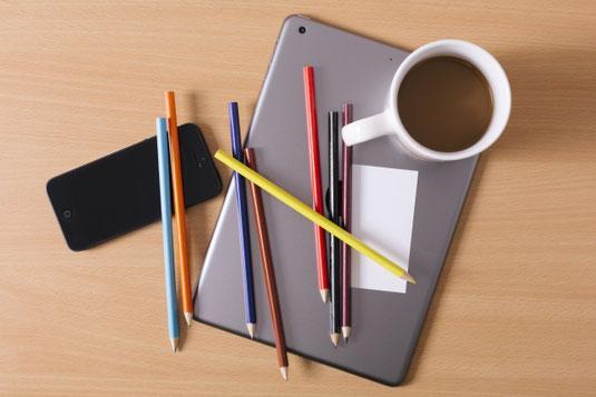 デスク周りのビジネスツール。ノートパソコンのうえに置かれたサインペンと電卓。卓上カレンダー、スマートフォン、マグカップ。
