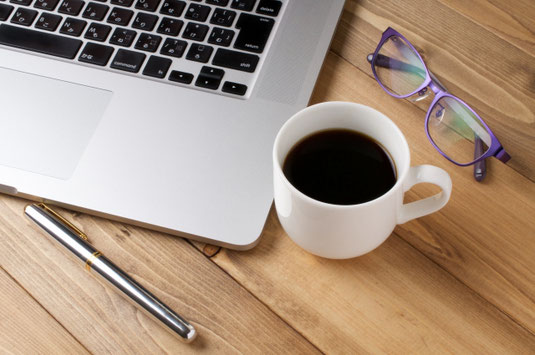 木目調のデスクの上に置かれたノートパソコン、ボールペン、リーディンググラス、コーヒーの入った白のマグカップ。