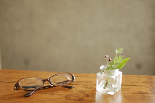 オフィスのテーブルに広げられたノートパソコン、メモ帳とボールペン、スマートフォン。テーブルの向こうに観葉植物。