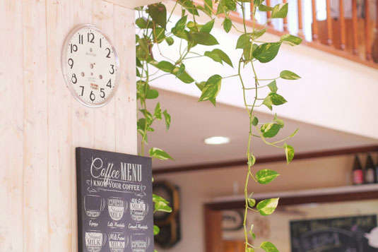 カフェのパートタイムジョブ。明るい店内。テーブルに置かれたアイスコーヒーとジャムトースト、ロールパン。
