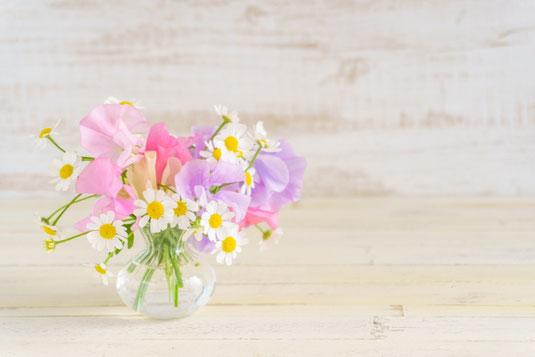 デスクトップパソコンのキーボード。レモンが浮かべられた紅茶の入ったカップ&ソーサ。黄色とオレンジのバラの花束。メモ帳とはさみ。観葉植物のグリーン。