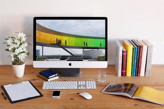 デスクトップ型パソコン。傍らにカラフルな背表紙の洋書、白い花の鉢植え、スマホなどが並んでいる。
