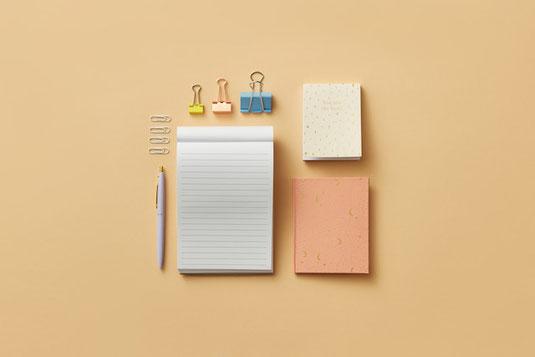 企画アイデアを書き留めたノート。ペン。スマホ。パソコンのキーボード。