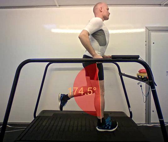 der Läufer joggt auf dem Laufband in seiner gewohnten Geschwindigkeit, er wird von der Seite aufgenommen, mit der Analysesoftware Dartfish werden mitlaufend die Beinwinkel gemessen