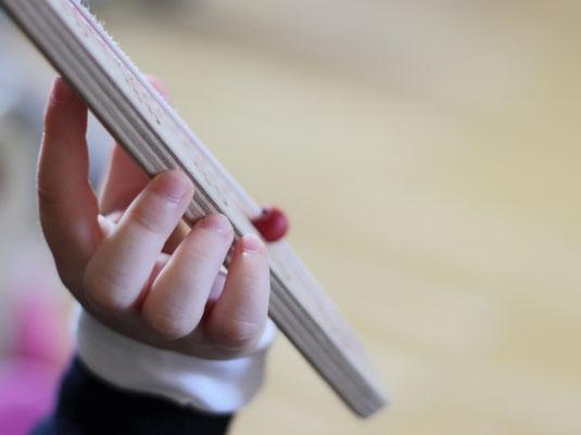 Ein Kindergartenkind hält ein Gefühlebarometer oder Gefühleregler in der Hand. Zu Beginn des Morgenkreises in seiner Kita darf es die Perle verschieben und erzählen, wie es sich heute fühlt.