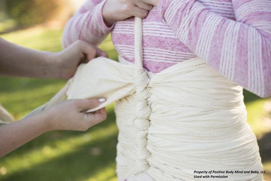 Das Bild zeigt eine Frau im Wochenbett, die gerade von einer anderen Frau mit einem langen naturfarbenem Schal eingebunden wird. Die Wöchnerin hält dabei den Schal um die Stabilität des Einbindens zu gewährleisten.