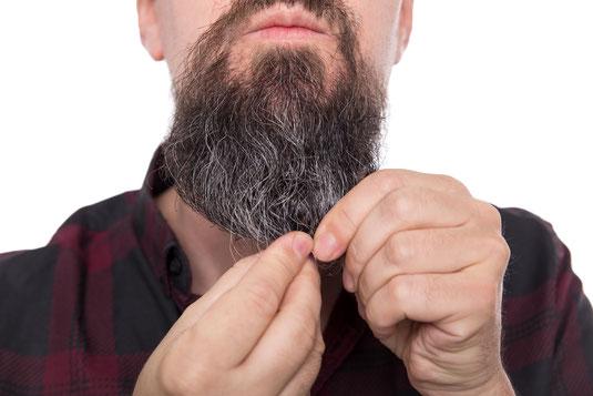 Mann masiert Bartöl ein