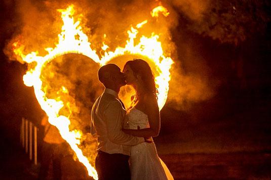Hochzeitspaar küsst sich bei Feuershow und Hochzeitsshows mit Feuerherz