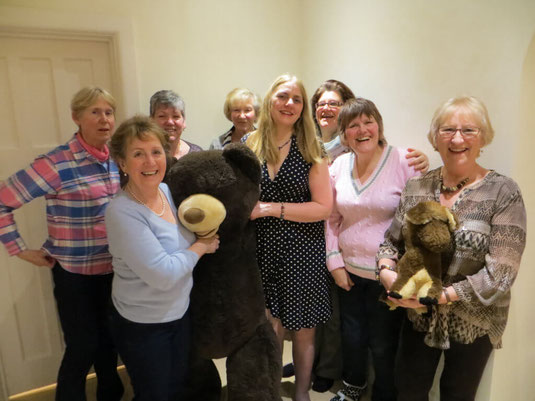 A group of Altos from the Wessex Chorus choir smiling with a giant teddy.