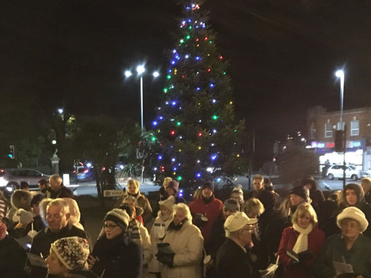 A group of carol singers around the Poole town hall Christmas tree.
