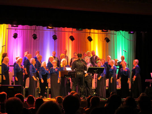 Wessex Chorus choir singing on the Barrington Theatre stage with rainbow coloured lighting.