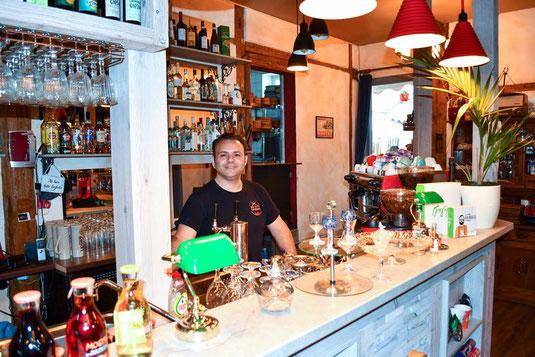 Ein Mann steht hinter der Theke eines griechischen Restaurants.