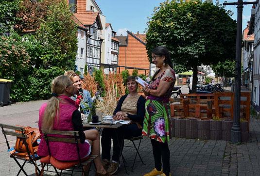 Eine Frau bedient drei Gäste in einem Straßencafé in Wolfenbüttel.