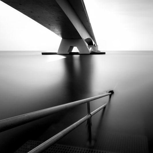 Zeeland Brücke (Zeelandbrug) in den Niederlanden in Schwarzweiß mit Geländer im Vordergrund